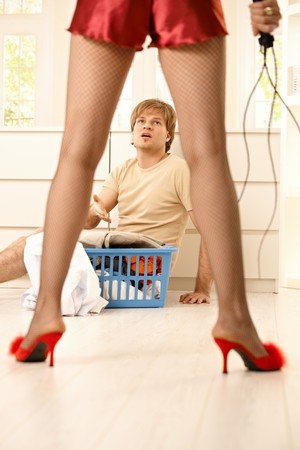 Woman wearing netted tights, sexy red baby-doll and high heels slippers holding lash forcing young man with laundry basket to do housework.  photo