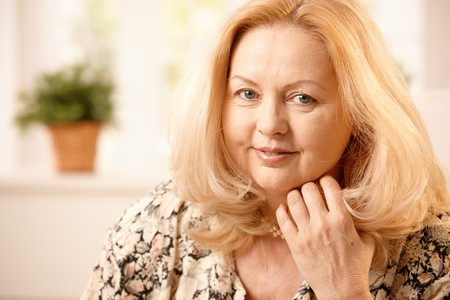sadece kadınlar: Closeup portrait of smiling senior woman with long blond hair at home.