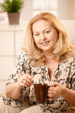 Happy senior woman stirring coffee with spoon, holding coffee mug, laughing at camera, sitting in living room. Stock Photo - 7249407