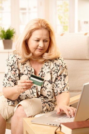 Elderly woman using computer for electronic shopping, typing on keyboard, holding creditcard, sitting in armchair. photo