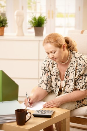 Mature blonde lady sitting at table in living room, taking notes on paper, looking down. photo