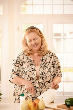 Mature blonde woman laughing at camera standing in kitchen, cooking, using bowl and egg whisk. photo
