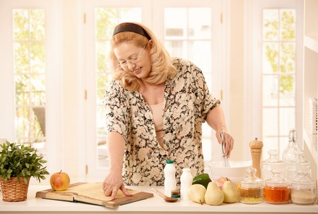 Senior woman cooking in kitchen, having vegetables and fruits around, reading recipe from book, holding egg whisk, smiling. photo