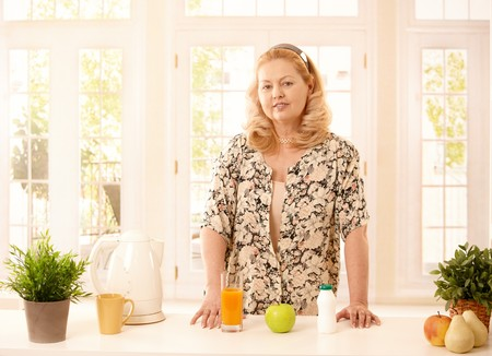 Older blonde lady standing at kitchen counter smiling at camera, presenting healthy orange juice, apple and yogurt.  photo