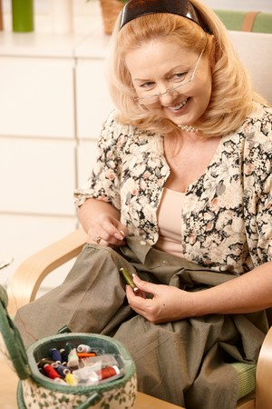 Smiling senior woman sitting in armchair, looking for matching colour of thread to shirt in sewing kit. Stock Photo - 7249423