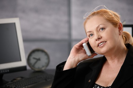 Senior businesswoman talking on cellphone at office desk, looking up, smiling. photo