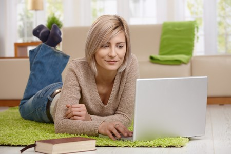 telecommuting: Attractive young at home in living room browsing internet on laptop computer, smiling.