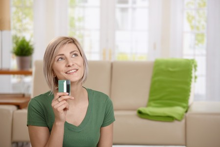 Young woman at home holding credit card looking up thinking about shopping.   photo