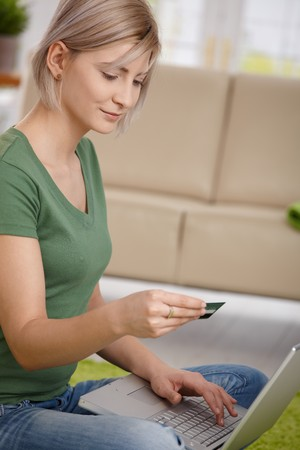 Young woman paying for online purchase with credit card and laptop. Stock Photo - 7257571
