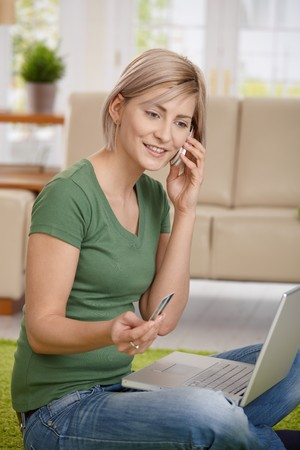 Woman paying bills from home with credit card, laptop and mobile phone. photo