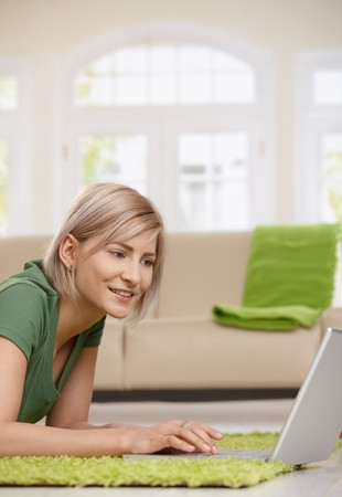 Happy blond woman at home browsing internet with laptop computer. Stock Photo - 7257503