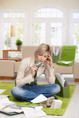 Troubled woman sitting on floor with crossed legs, looking at documents holding credit card in living room. Stock Photo - 7257555