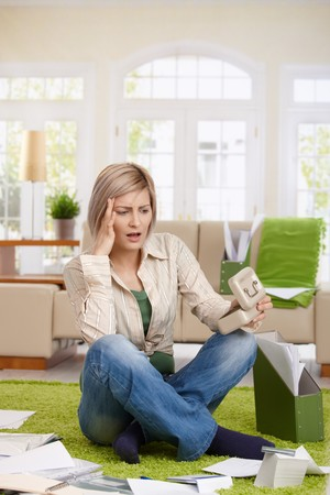 Shocked woman sitting at home surrounded with documents, looking at money box unbelieving. photo