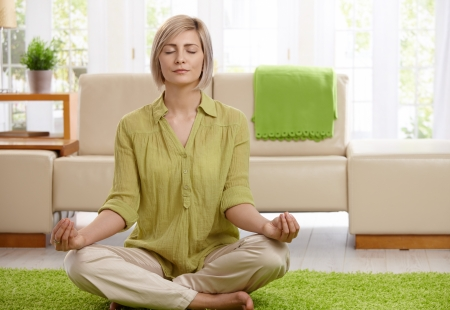meditating woman: Woman sitting on floor at home doing yoga meditation. Stock Photo