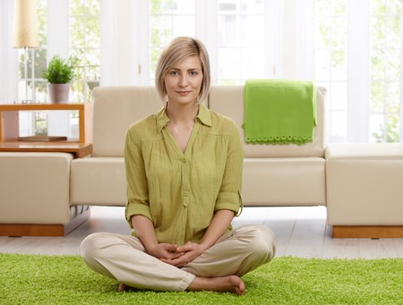 Smiling woman sitting with legs crossed on living room floor, looking at camera. photo