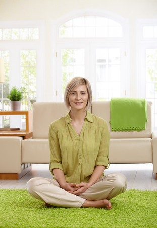Happy  woman sitting with legs crossed on living room floor, looking at camera. photo