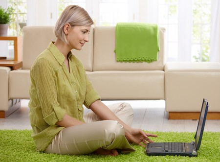 woman sitting floor: Smiling woman sitting on living room floor working on computer.