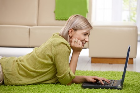 good mood: Smiling woman lying on floor at home looking at laptop screen, typing. Stock Photo