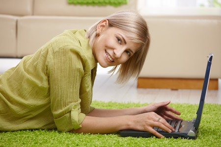 Smiling woman looking at camera, lying on floor of living room using computer. Stock Photo - 7257605