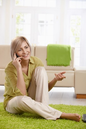 Cheerful woman speaking on mobile phone, sitting on living room floor, gesturing with hand. photo