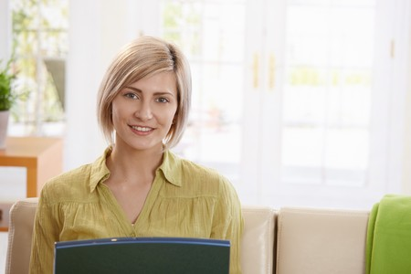 Portrait of woman looking at laptop computer sitting on sofa at home, smiling. photo