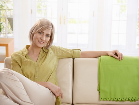 Portrait of young blonde woman sitting on sofa at home, looking at camera smiling. Stock Photo