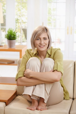 pulled: Attractive woman sitting on living room sofa with knees pulled up and arms around legs, smiling at camera. Stock Photo