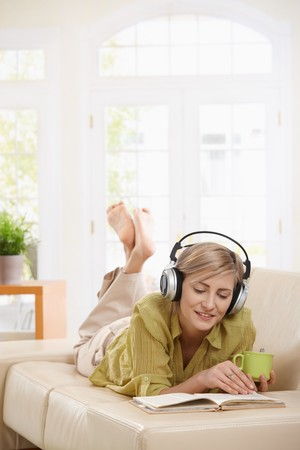 Woman  lying on couch at home drinking coffee, reading book, listening music in headphones. Copyspace on top. photo