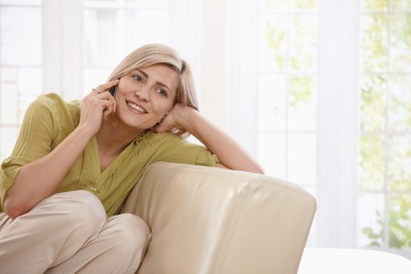 attractive couch: Happy blonde woman sitting on sofa at home, calling with mobile phone smiling.