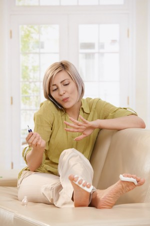 Woman sitting on couch drying nail polish on hand, listening to phone call.