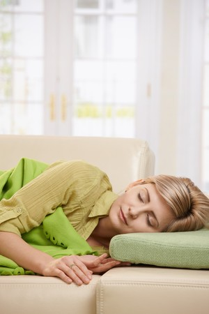 Blond woman sleeping with blanket on couch in sunlit living room at home. photo