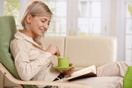 reading room: Woman sitting in armchair, reading book, holding coffee mug, smiling.