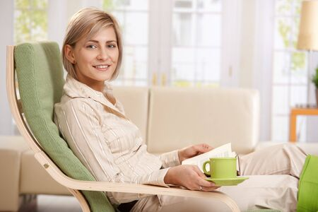 Woman relaxing in armchair at home, reading book , holding coffee cup. photo