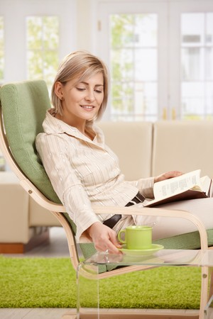 Woman relaxing in armchair at home, reading book, putting coffee on table, smiling. photo