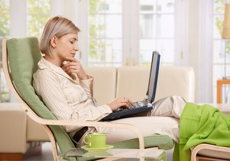 Woman sitting in armchair with feet up working with computer at home in living room. photo