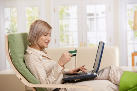 buy online: Young woman sitting in armchair at home typing on laptop keyboard, looking at credit card in hand, smiling.