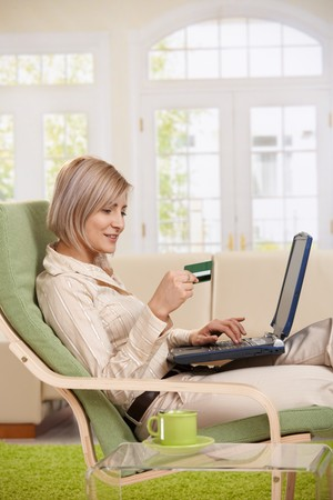Young woman sitting in armchair at home typing on laptop keyboard, looking at credit card in hand, smiling. photo