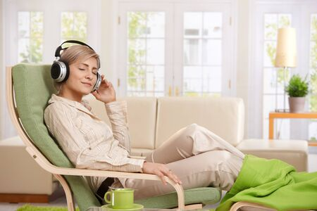 Woman relaxing in armchair at home enjoying music in headphones, smiling. photo
