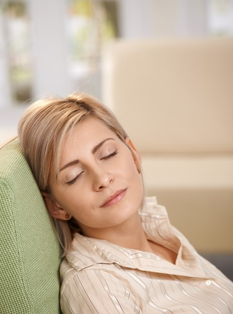Woman napping at home sleeping in armchair enjoying afternoon sunshine. Stock Photo - 7257554
