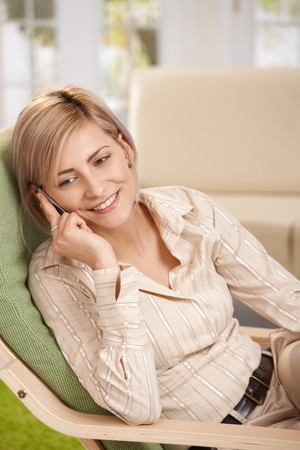 Happy casual woman resting at home talking on mobile phone, smiling. photo