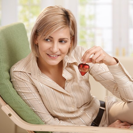 Smiling woman sitting in armchair holding up small red heart, looking aside. photo