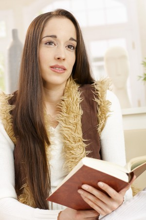 Young woman looking up from book handheld, daydreaming, smiling in bright living room. photo