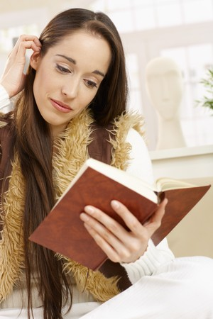 Young woman reading a book handheld in living room, smiling. Stock Photo - 7263676
