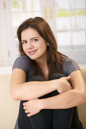 Portrait of smiling girl sitting on sofa with arms around legs pulled up, looking at camera. photo
