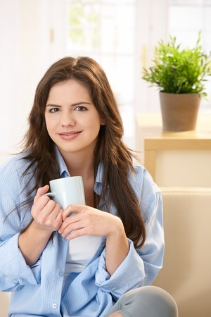 Pretty young woman sitting on couch at home in morning sunlight holding mug, looking at camera, smiling. photo