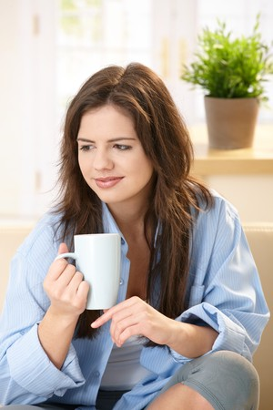 Pretty girl sitting at home holding coffee mug, smiling. photo
