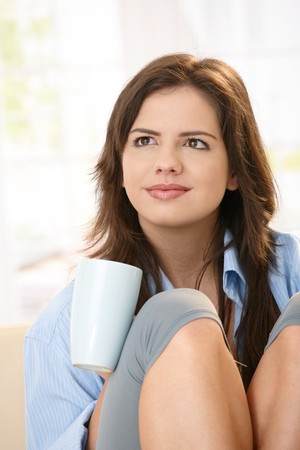 Portrait of smiling girl holding coffee cup, sitting with knees pulled up in closeup. photo