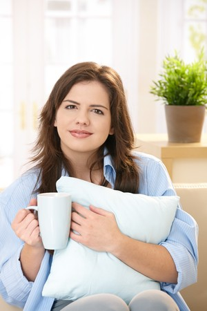 Pretty girl sitting on couch holding morning coffee in one hand and pillow in other,  smiling at camera. photo