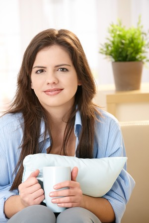 Girl smiling at camera holding coffee mug with two hands, pillow in arms, sitting on couch. photo