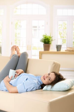 Young woman lying on sofa with feet up holding coffee mug in hand, smiling. photo